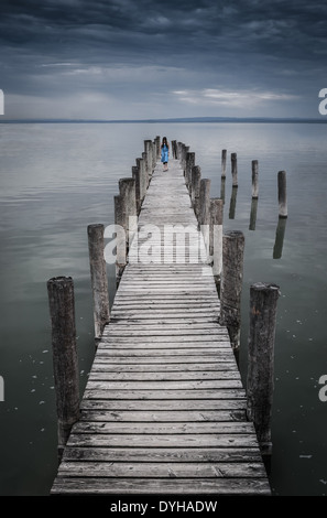 Scary longhaired girl in blue dress walking on the pier in eerie atmosphere - Stock Photo