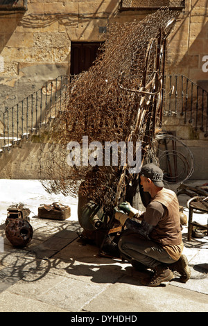 Artist creating a bike artwork from rusty materials in the city center of Salamanca, Castilla y León, Spain. - Stock Photo