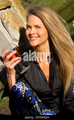 beautiful blonde middle aged woman drinking a glass of wine in the sunshine - Stock Photo