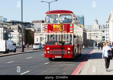 Open top tour bus with passengers passing over London Bridge, England - Stock Photo