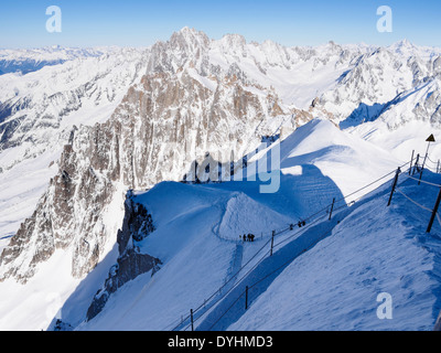 Roped path route to Vallee Blanche with skiers descending on Aiguille du Midi. Chamonix-Mont-Blanc Rhone-Alpes France - Stock Photo