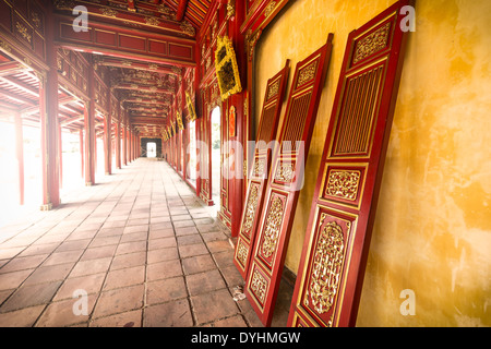 Beautiful red wooden hall with golden ornate details in Hue citadel, Vietnam, Asia. Vanishing roof and tiled floor. - Stock Photo