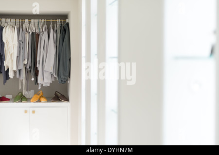 Row of new casual clothing on hangers at shop with four colorful pairs of shoes under it. Clothes presented as in - Stock Photo