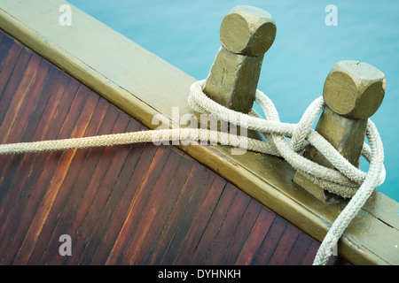 Marine rope tied into knot in foreground, white background. Close-up of nautical equipment for mooring. Focus on - Stock Photo