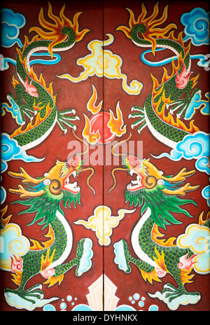 Bright colorful painting with dragons on door of building in Vietnam. Double folding ancient doors with symmetric - Stock Photo