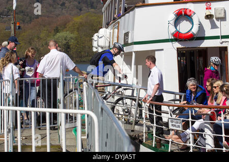 Lake Windermere, Cumbria, UK. 19th April 2014. Tourists making the most of sunshine Cyclists letting the boat take - Stock Photo