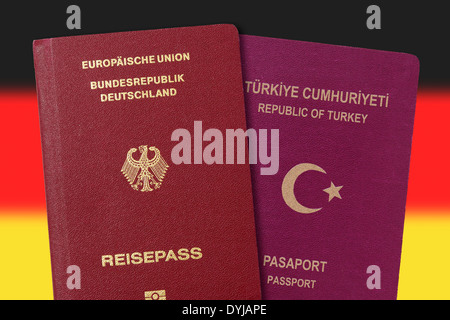 German and Turkish passport in front Germany flag, dual citizenship - Stock Photo