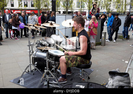 Manchester, UK. 19th April 2014. A street musician plays his music in front of passers-by in Piccadilly Gardesn, - Stock Photo