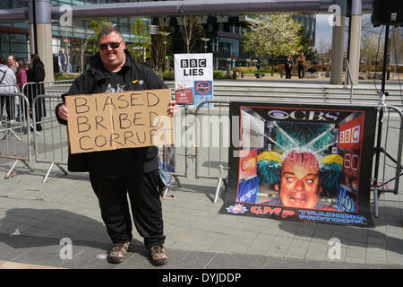 MANCHESTER, UK Saturday 19th. April 2014. Protester holding sign stating the BBC is Corrupt and biased with banner - Stock Photo
