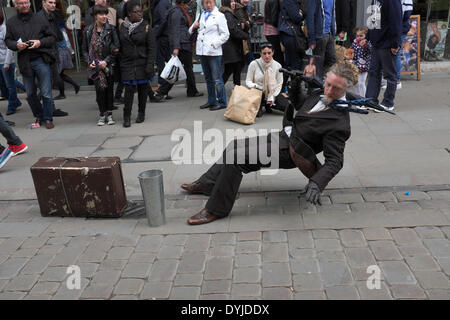 Manchester, UK. 19th April 2014. A gravity-defying street performer shows his skill in front of passing shoppers - Stock Photo