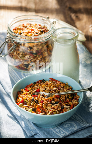 Serving of homemade granola in blue bowl and milk or yogurt on table with linens - Stock Photo