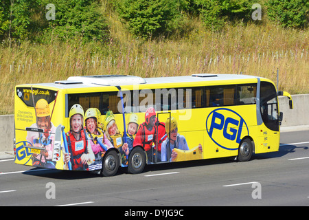 Advertising promoting adventure travel for school children on side and back of coach driving along motorway - Stock Photo