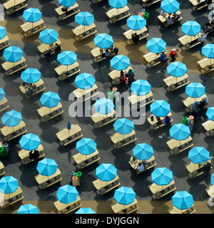 Colourful parasols shading picnic tables with one not open (odd one out) - Stock Photo