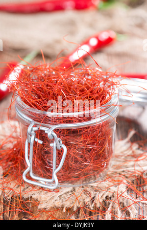 Small portion of dried Chilli Strings on wooden background - Stock Photo