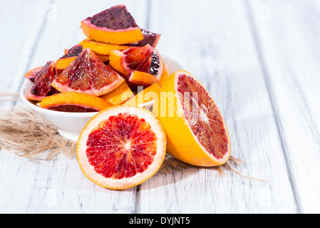 Portion of fresh and juicy Blood Orange on wooden background - Stock Photo