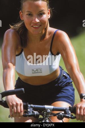 Sportliche junge Frau unterwegs mit dem Fahrrad - Stock Photo