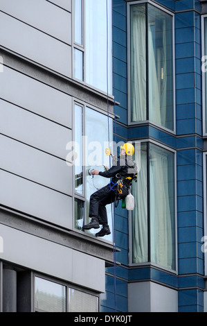 Window cleaner using industrial rope access techniques at work on an office building, London Road, Manchester, England, - Stock Photo
