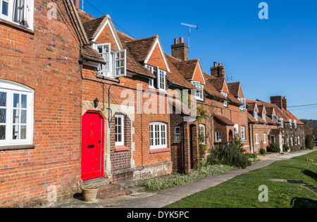 Bright red front door in row of cottages in the village of Great Bedwyn, Wiltshire, UK, many now second homes or - Stock Photo
