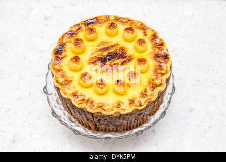 Traditional home baked round simnel cake for Easter, topped with marzipan, on glass plate - Stock Photo