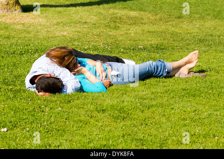 A young couple taking a nap on a lawn. - Stock Photo
