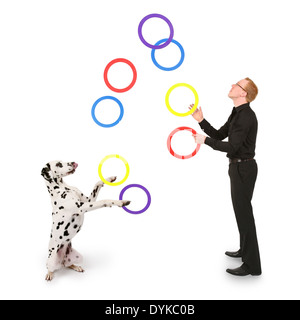 junger Mann jongliert mit Ringen, young man juggling with rings, Mann spielt mit Dalmatiner - Stock Photo