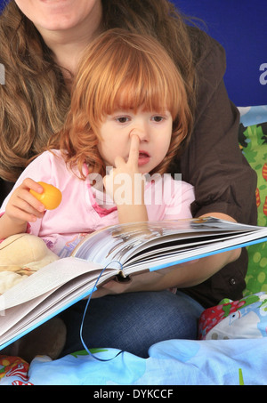 little red-haired girl listen to a bedtime story picking her nose - Stock Photo