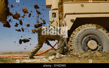 US Air Force Staff Sgt. Kyle McGann digs out a mine-resistant, ambush-protected vehicle from spring mud March 16, - Stock Photo