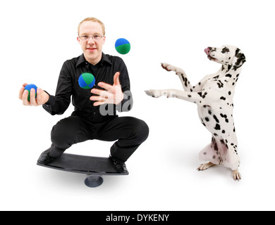 young man juggling with balls and balancing on a rola bola balance board, Mann spielt mit Dalmatiner - Stock Photo