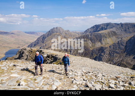 Two hikers climbing up Y Garn with view to Tryfan and Glyderau in mountains of Snowdonia National Park Ogwen Gwynedd - Stock Photo