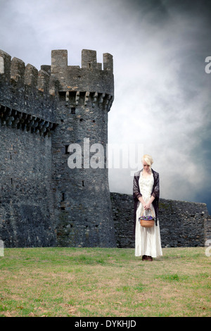a woman in a white period dress is standing in front of a castle - Stock Photo
