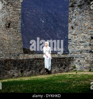 a woman in a white period dress is sitting on a wall at a castle - Stock Photo