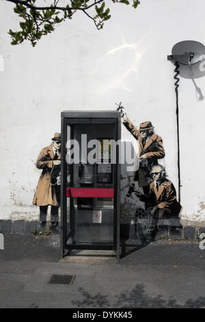 This piece of street art is believed to be by Banksy, it features eavesdropping agents crowded around a telephone - Stock Photo