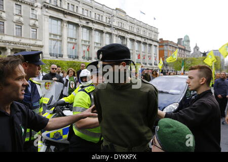 Dublin, Ireland. 21st April 2014. Garda (Irish police) officers move a member of the Republican Sinn Fein colour - Stock Photo