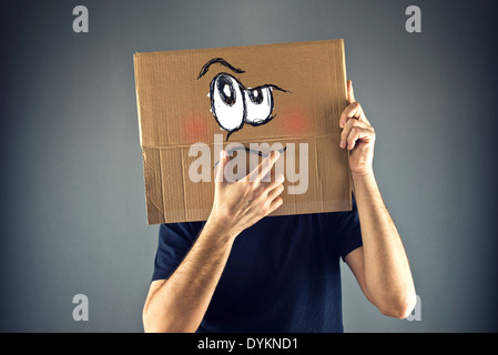 Man thinking with cardboard box on his head with serious face expression. - Stock Photo