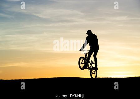 Young Man doing a wheelie on his BMX bike. Silhouette - Stock Photo
