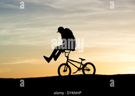 Young Man doing tricks on his BMX bike. Silhouette - Stock Photo