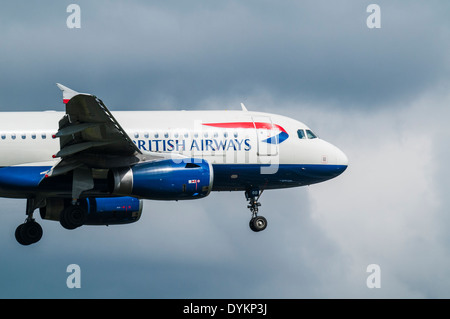 Side view of a British Airways Airbus A319 aircraft on approach to land with landing gear down - Stock Photo