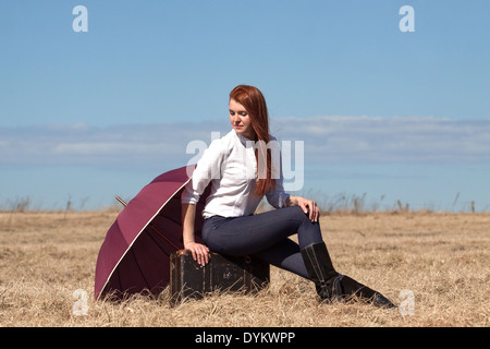 Red haired girl with vintage bag and umbrella - Stock Photo