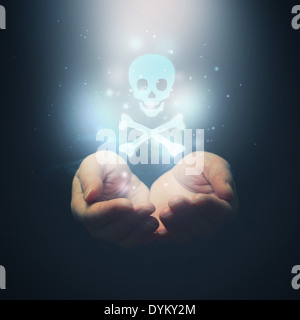 Female hands opening to light and skull as symbol of poison or something deadly and dangerous - Stock Photo