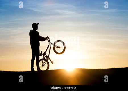 Young Man holding his BMX bike with sun lens flare. Silhouette - Stock Photo