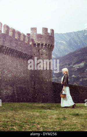 a woman in a white period dress is walking along a castle - Stock Photo