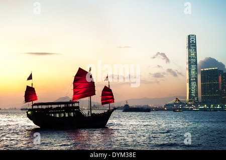 Traditional junk crossing Victoria Harbour, Hong Kong - Stock Photo