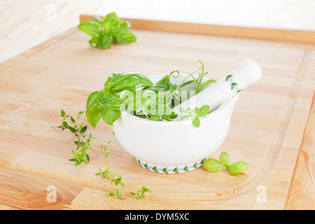 Culinary aromatic herbs in mortar with pestle on wooden chopping board on wooden background. Fresh cooking ingredients. - Stock Photo
