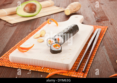 Traditional sushi rolls on wooden board. - Stock Photo