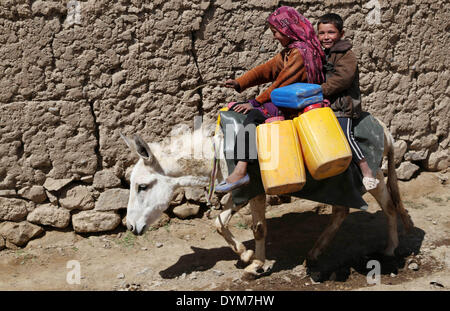 Bamyan. 22nd Apr, 2014. Afghan children ride a donkey while carrying empty barrels to get water in Bamyan province - Stock Photo
