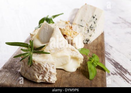 Luxurious goat cheese variation and blue cheese on wooden kitchen board on white wooden background. Luxurious cheese - Stock Photo