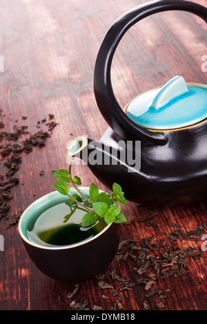 Traditional tea background. Tea in tea bowl with fresh mint herb, ceramic tea pot, dry tea crop on brown wooden - Stock Photo