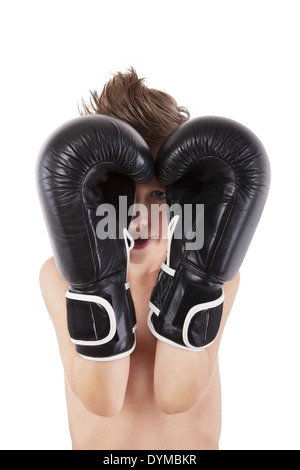 Young caucasian boy with boxing gloves protecting his face against white background. Small charming fighter. - Stock Photo
