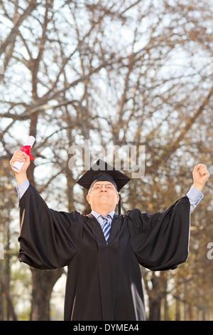 Mature college graduate gesturing success outdoors - Stock Photo