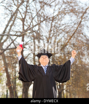 Mature graduate holding diploma and gesturing happiness outdoors - Stock Photo